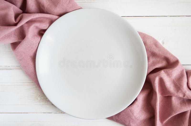 Wooden white table with mint napkin of pink color with an empty plate royalty free stock photography