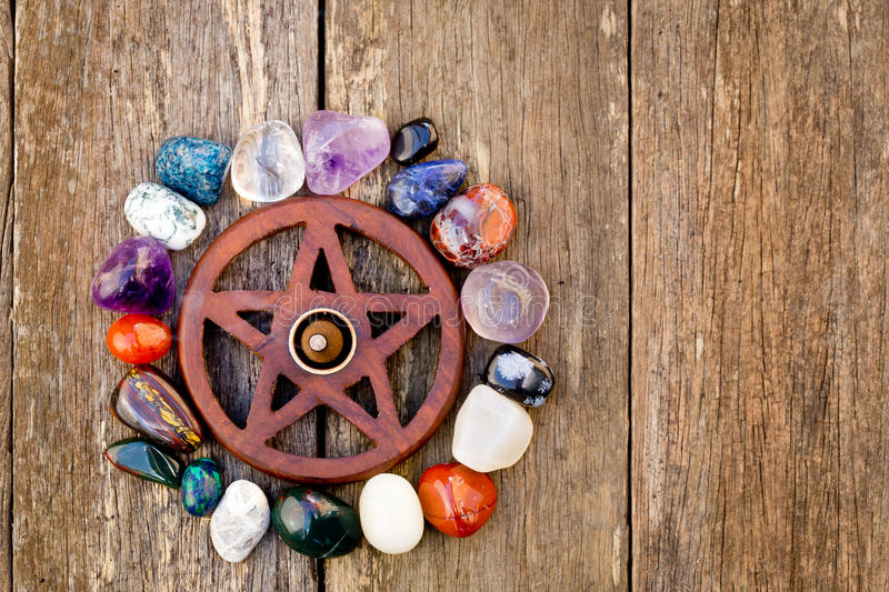 Wooden wiccan pentagram with incense burning surrounded by crystals - on wooden background stock images