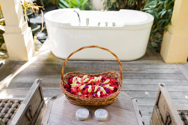 Wooden wicker basket with flowers for beauty spa. Wooden wicker basket with red and white flower petals in front of white stone empty bath over green tropical stock images