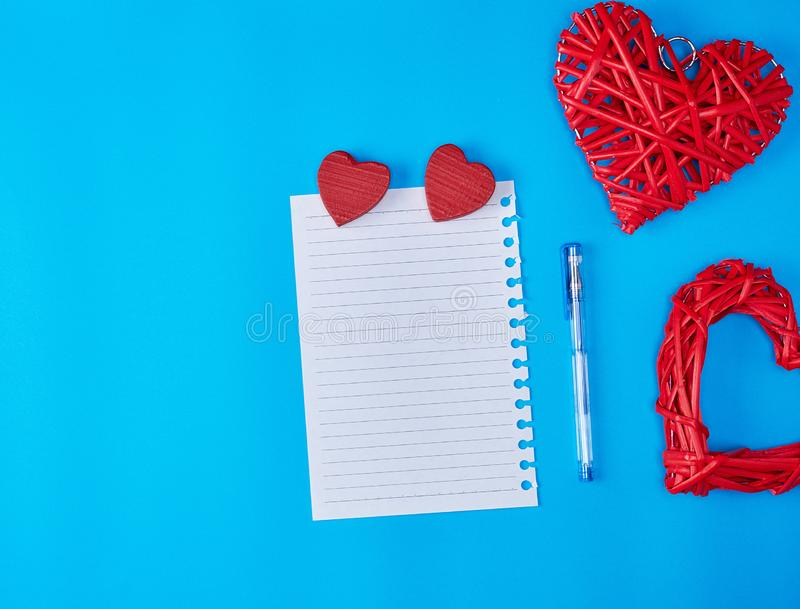 Wooden wicker red heart and an empty white sheet of notepad. Blue background stock photos