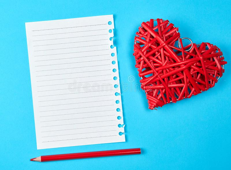 Wooden wicker red heart and an empty white sheet of notepad. Next to a pencil, blue background royalty free stock photography