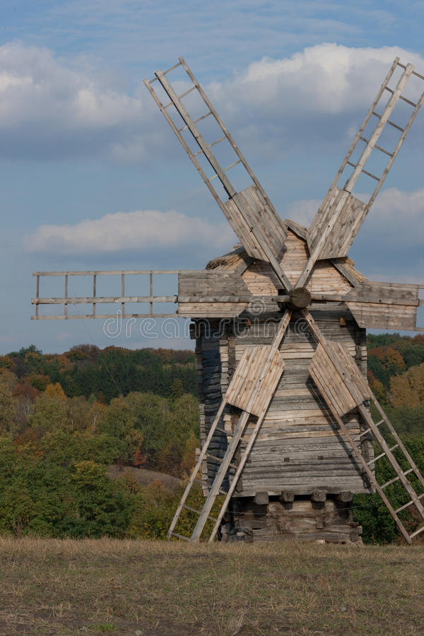 Wooden windmill. Autumnal forest. royalty free stock image
