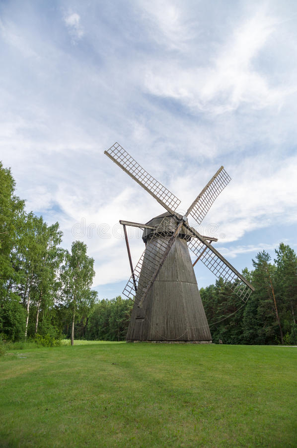 Wooden windmill on green grass field under blue sky. Vertical view stock image