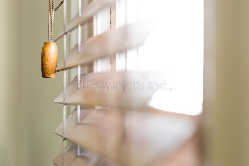 Wooden window blinds partially closed with bright light. Going through. Close up detailed crop, side angle perspective, shallow depth of field stock images