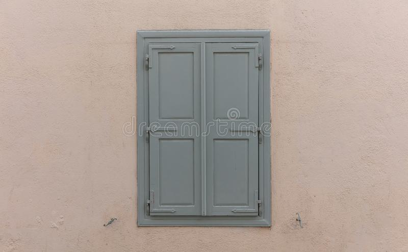 Wooden window with grey shutters, closed, on painted wall background stock photos