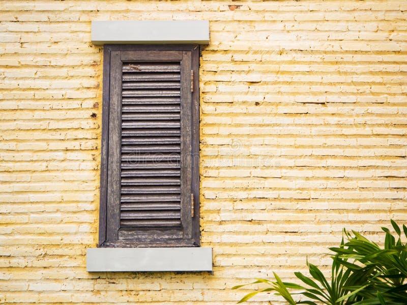 Wooden window on yellow brick wall. Vintage wooden window on the yellow brick wall stock photos