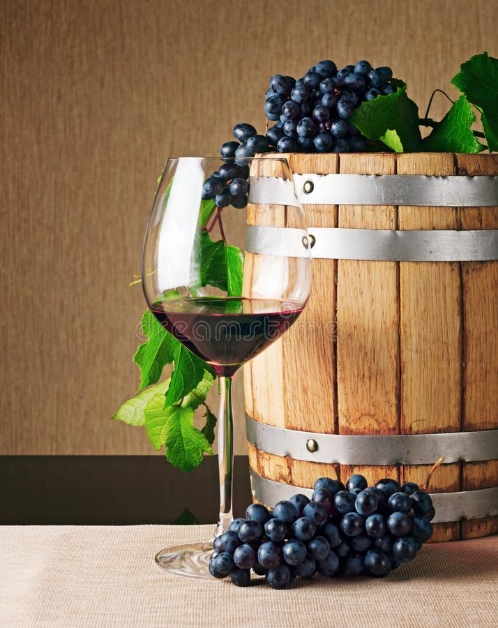 Wooden wine barrel and glass of red wine on table. Glass of red wine, wooden wine barrel and bunches of ripe grape on table. Winemaking product. Classical royalty free stock image