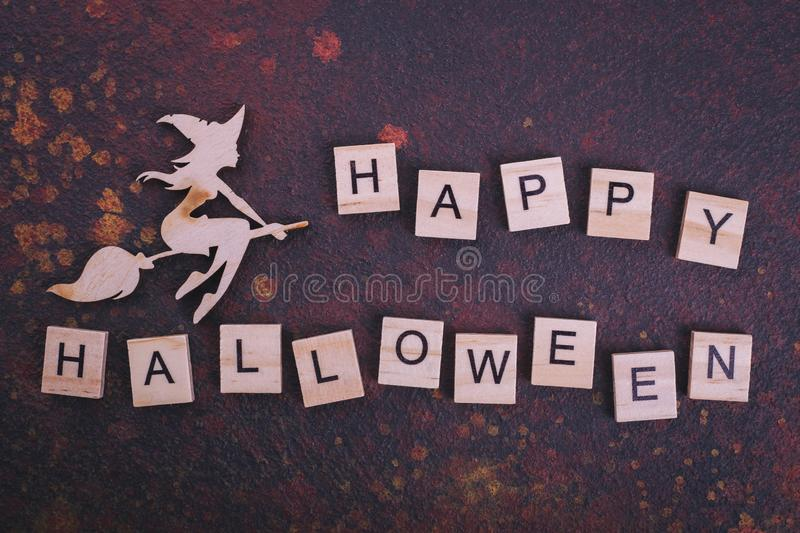 Wooden witch, text Happy Halloween. Figurine, congratulations with Halloween from wood stock photo