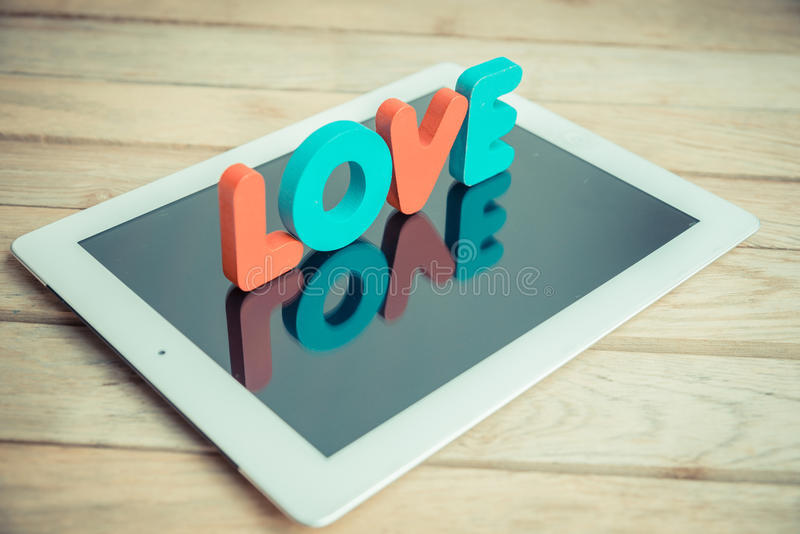 Wooden word LOVE stand on tablet in vintage style. 3 stock photos