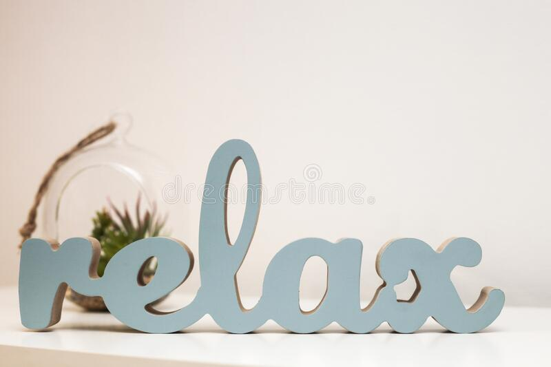 Wooden word Relax and plant in pot, home details, on wooden table stock photography