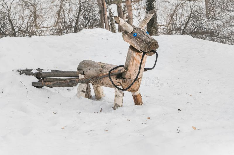 A wooden yellow horse or donkey with a carriage for children on the playground in the winter park royalty free stock photos
