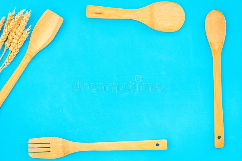 Woodenware set with spoon, fork on blue backgtound top view space for text. Woodenware craft set with spoon, fork on blue backgtound top view space for text stock image