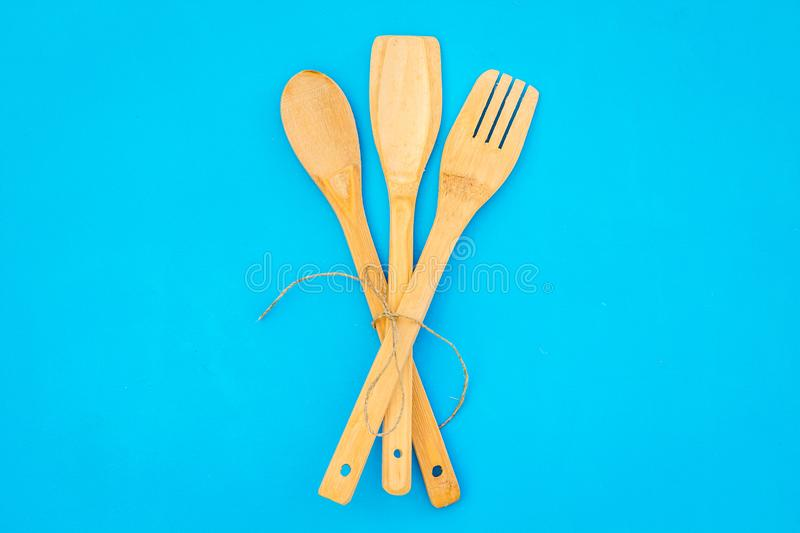Woodenware set with spoon, fork on blue backgtound top view space for text. Woodenware craft set with spoon, fork on blue backgtound top view space for text royalty free stock image