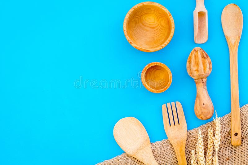 Woodenware set with spoon, fork and bowl on blue backgtound top view space for text. Woodenware craft set with spoon, fork and bowl on blue backgtound top view royalty free stock photo