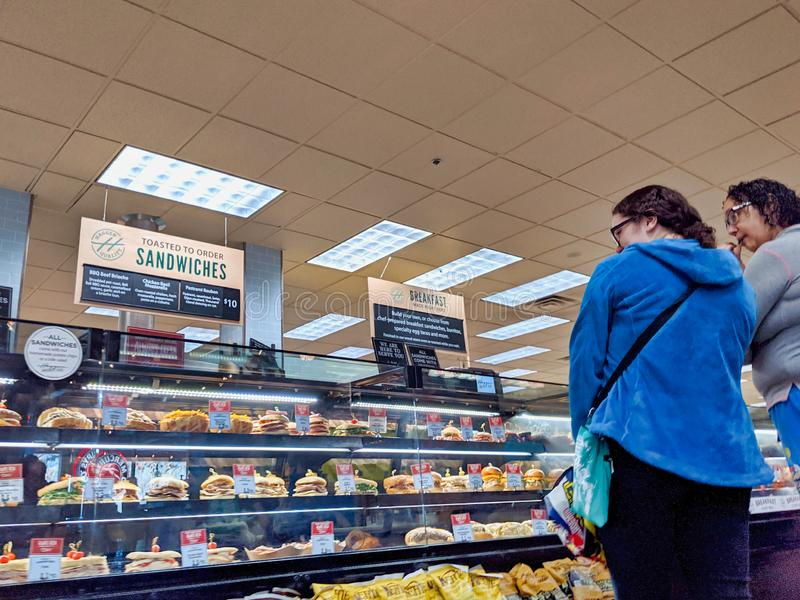Customers shopping at the deli department in a Haggen Northwest Fresh grocery store. Woodinville, WA / USA - November 2nd, 2019: Customers shopping at the deli stock photography