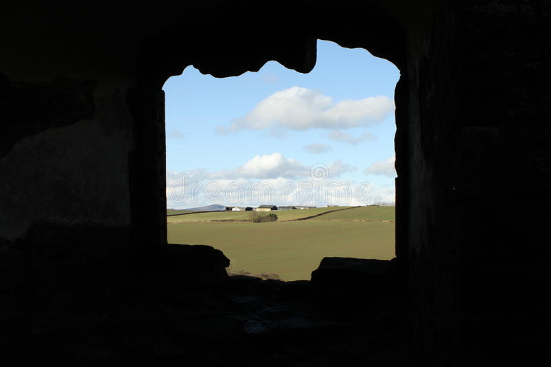 Looking through the ancient window. Looking through the ancient, silhouetted window to a beautiful countryside view royalty free stock photography