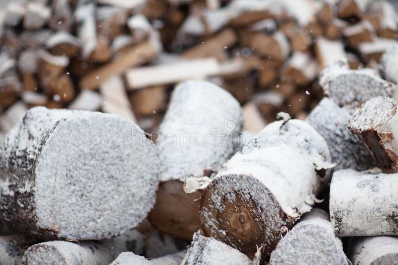 Woodpile with birch firewood. Snow Covered Firewood stock photo