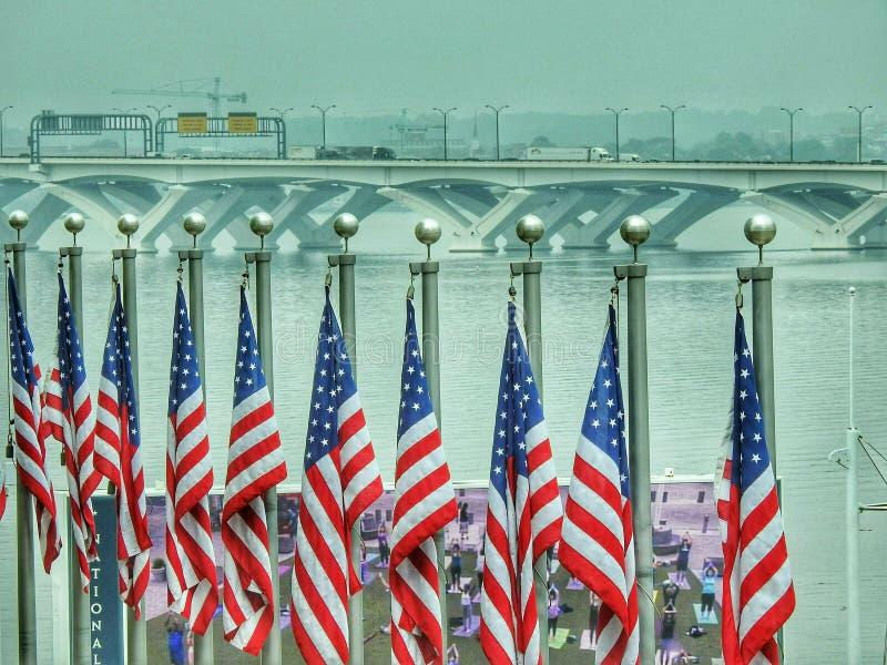 Woodrow Wilson Bridge And United States Flags Over The Potomac River. Maryland, dc, washingtondc, flagpoles, red, white, blue, travel, national, harbor, water royalty free stock image