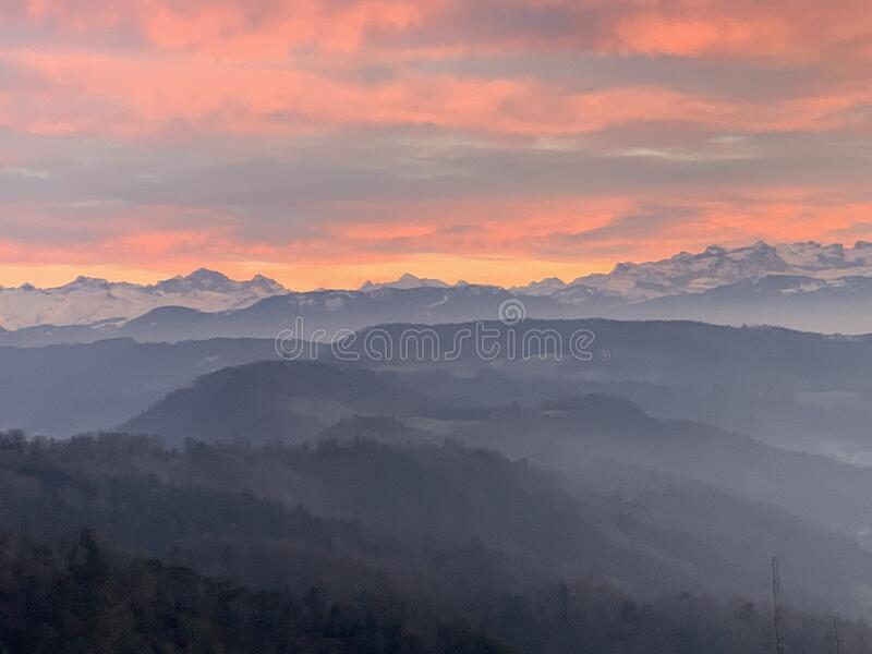 Woods surrounding Uetliberg at sunset in winter with Alps on the horizon, district Zurich Switzerland. The sky of yellow pink and orange hues casts soft light royalty free stock images