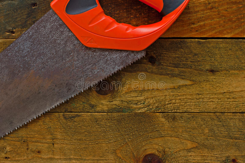 Woodsaw on rustic wooden work bench. Red woodsaw on rustic wooden work bench royalty free stock photos