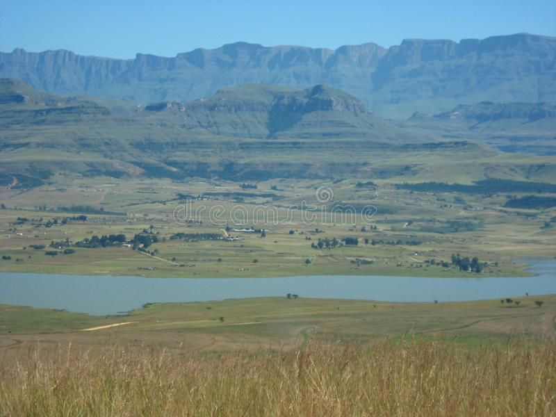 The Woodstock dam framed by the Drakensberg mountain range. The Drakensberg mountain range, so named for the dragon-like ridges along it`s length, towers over stock photos