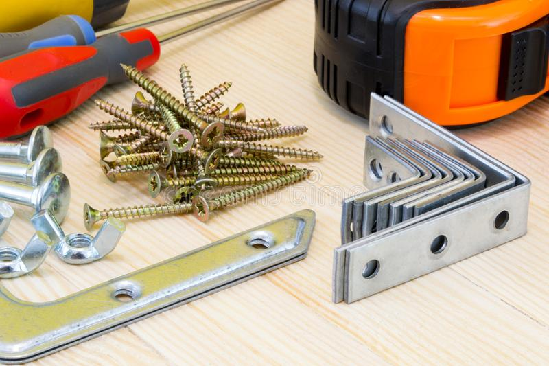 Woodwork tools and screws at the wood planks on yellow background royalty free stock photography