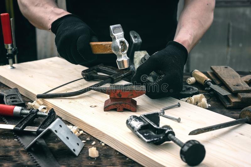 Woodwork. Worker bends a nail on the anvil. Woodwork concept. Carpentry, hammer, carpenter, table, tools, man, person, background, workbench, workplace, wooden stock photography
