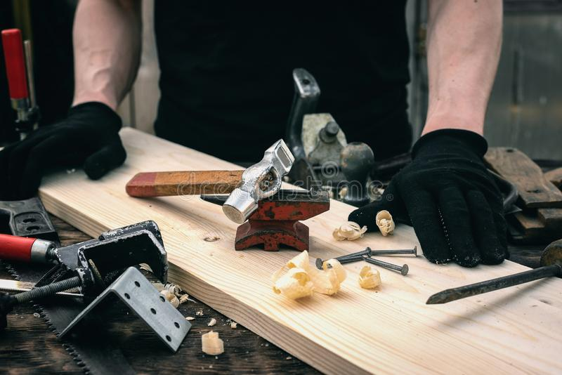 Woodwork. Worker bends a nail on the anvil. Woodwork concept. Carpentry, hammer, carpenter, table, tools, man, person, background, workbench, workplace, wooden royalty free stock image