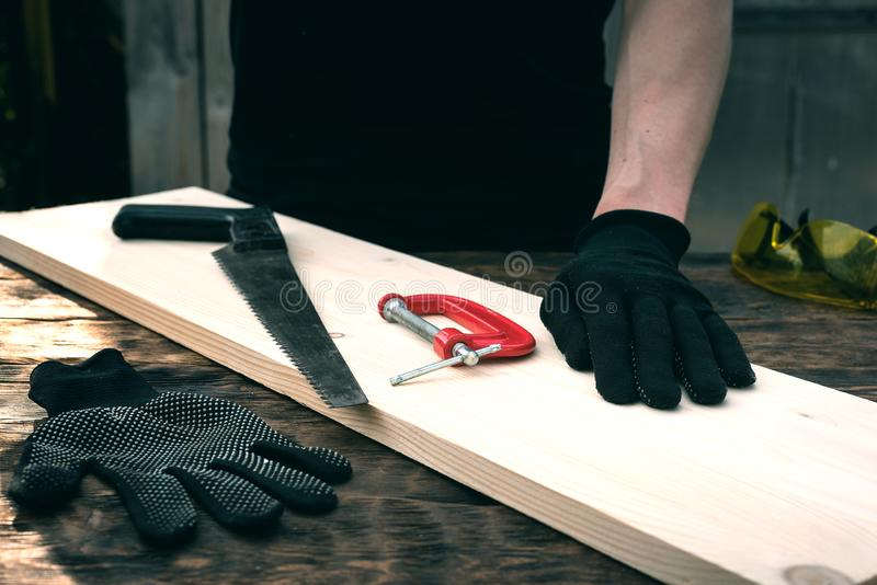 Woodwork. Worker is holding a wooden bar on a workbench. Woodwork. Carpentry, carpenter, table, tools, man, person, background, abstract, above, top, view stock images