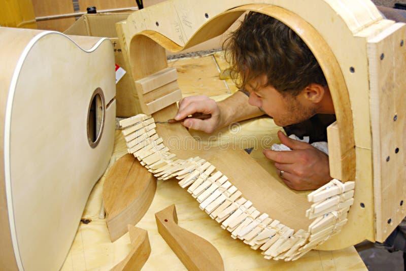 Woodworker κιθάρα οικοδόμησης στο εργαστήριο στοκ φωτογραφία