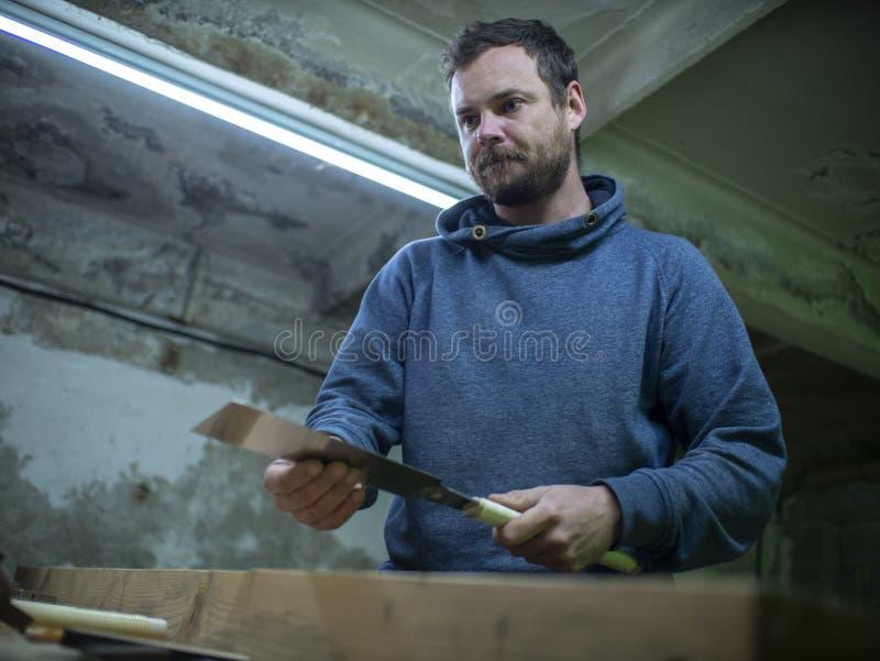 Woodworker με μια γενειάδα που πριονίζει μια ξύλινη ακτίνα με ένα πριόνι χεριών ένας ξυλουργός που πριονίζει ένα κομμάτι του ξύλο στοκ εικόνα