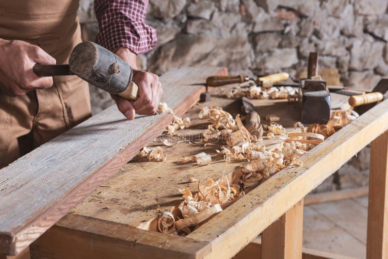 Woodworker используя зубило для того чтобы приглаживать вниз с древесины стоковые фотографии rf