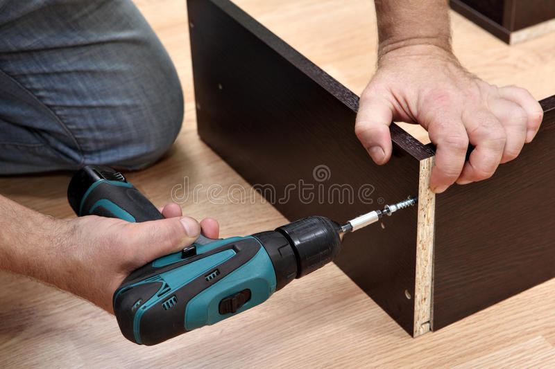 Woodworker Assembling Furniture made of chipboard using a cordless screwdriver. stock photo