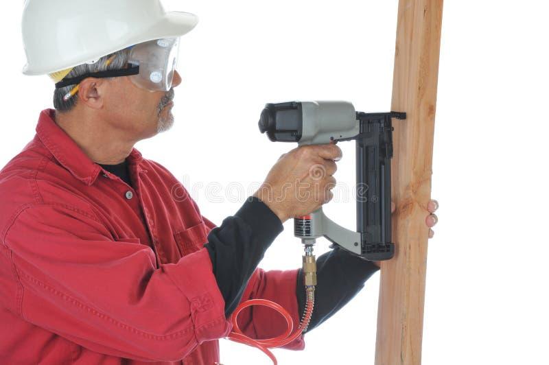 Woodworker, der Nagel-Gewehr verwendet stockfotografie