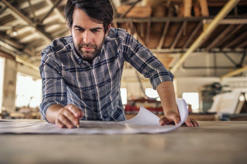 Woodworker iść nad projektów planami na warsztatowej ławce zdjęcia stock