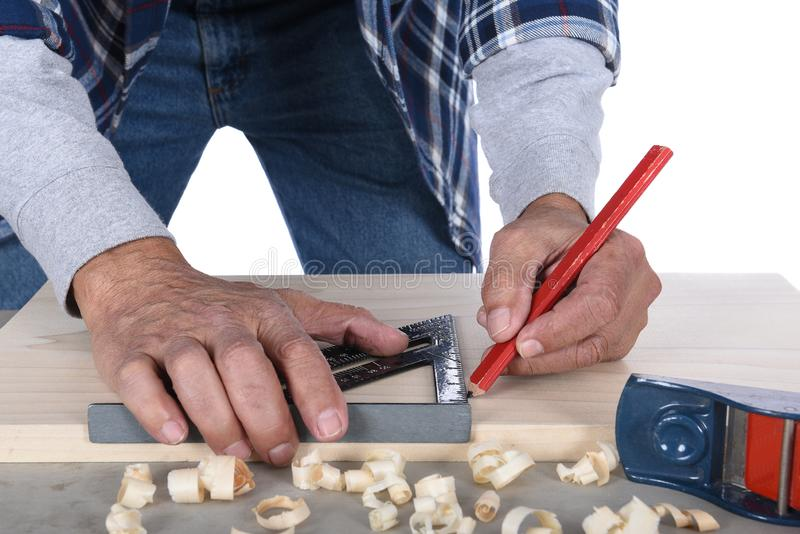 Woodworker marking a cut line on a board. Man is unrecognizable, isolated on white stock photography