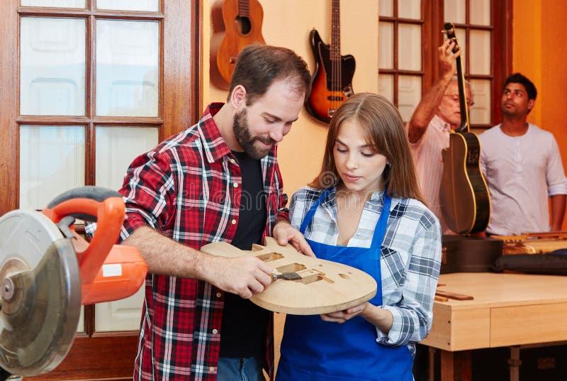 Woodworker pokazuje aplikant gitary budynek zdjęcie stock