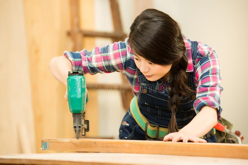 Woodworker using air compressor nail. Wooden carpenter carefully using air compressor nail gun in workshop studio. mixed race asian chinese model stock image