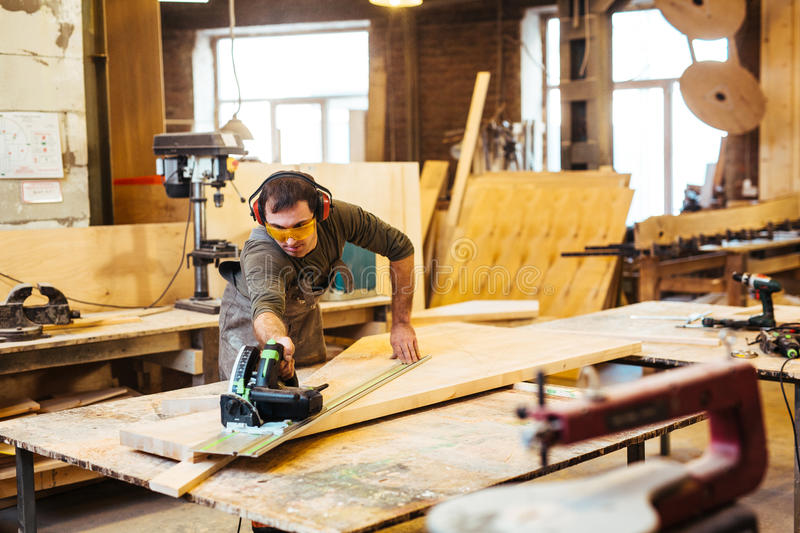 Woodworker. Woodworking artisan cutting wooden plank stock images