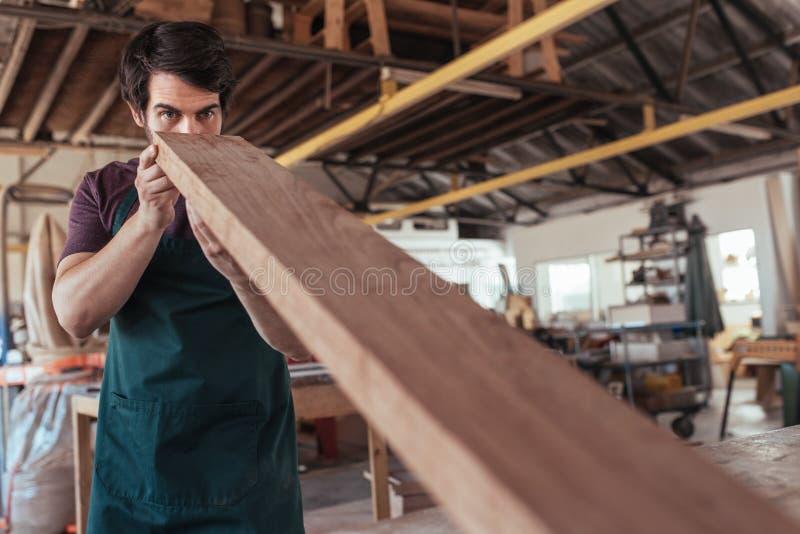 Woodworker zręcznie egzamininuje deskę drewno w jego warsztacie obraz royalty free