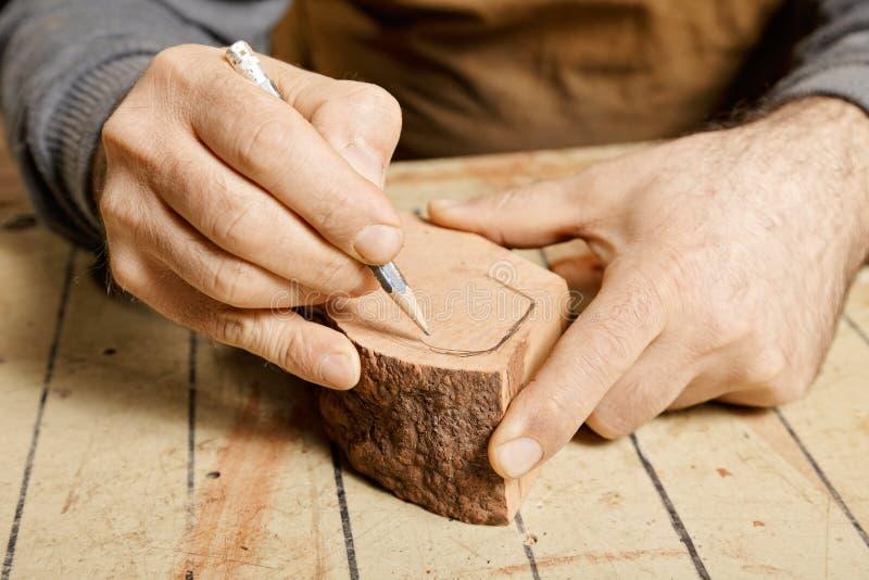 Woodworkerhände, die auf hölzernem Billet skizzieren lizenzfreies stockbild