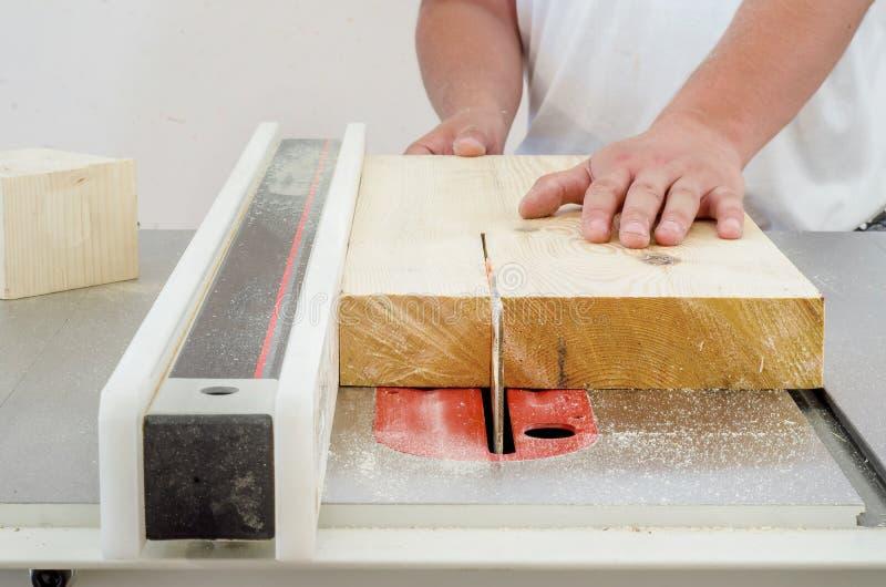 Woodworking, mężczyzna ciie deskę na kurendzie zobaczył maszynę fotografia stock