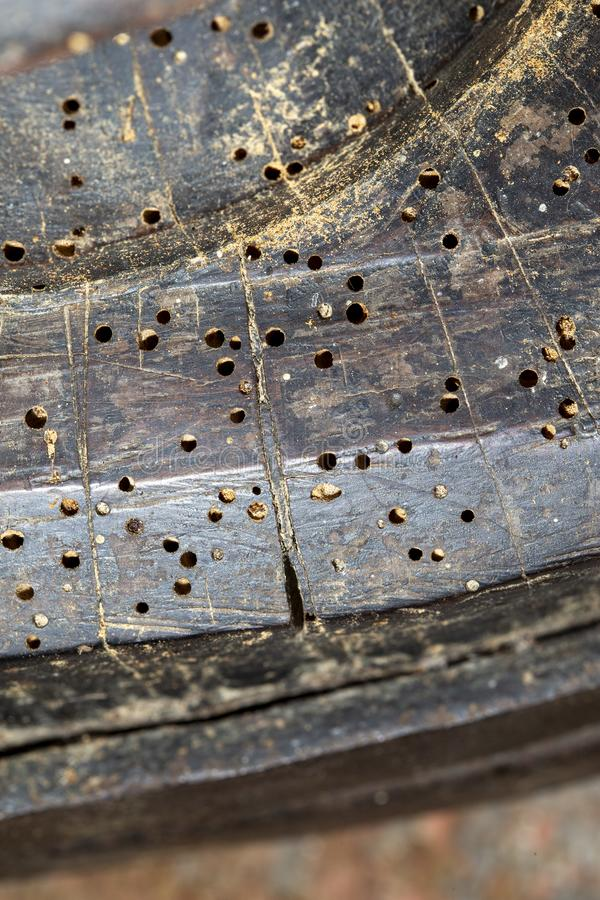 Woodworm holes in old furniture. Closeup shot of woodworm holes in an old piece of furniture stock images