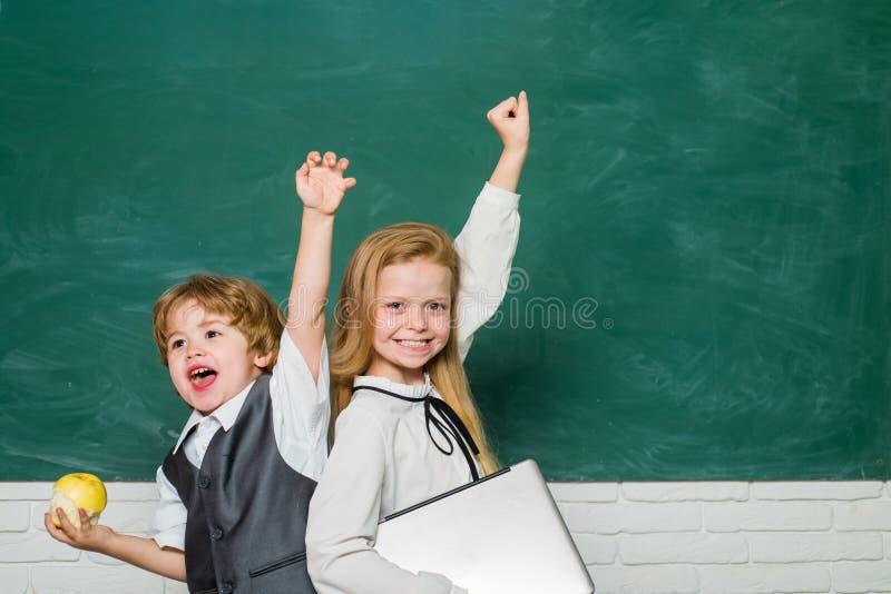 Woohoo Bambino sorridente allegro alla lavagna scolaro Scuola e bambini del libro Aula Lezioni della scuola yeah fotografia stock