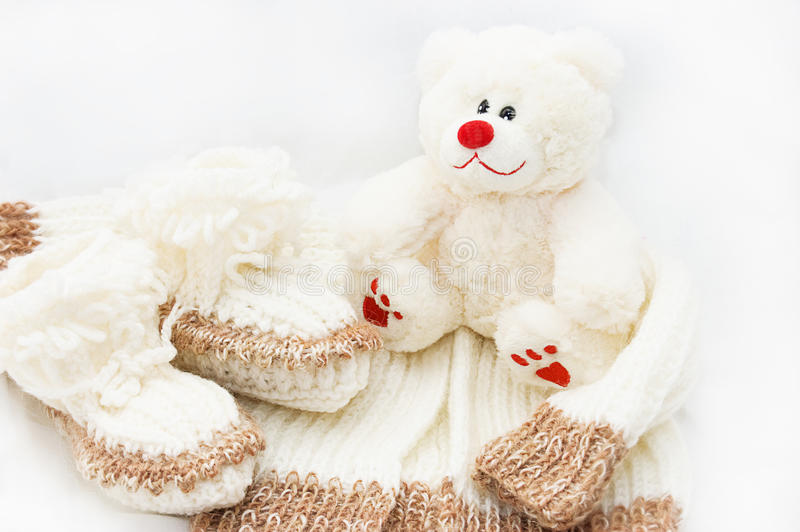 Wool hand-made baby coat, socks and teddy bear stock image