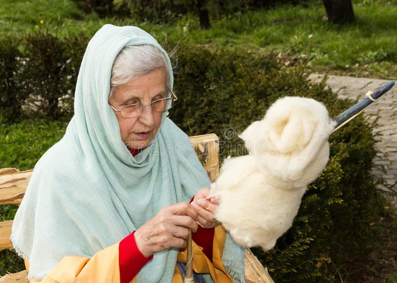 The Wool Spinner. Woman spinning thread with the wool in Biblical Village. The Biblical Village is the first project in Europe organized in Bucharest at Titan royalty free stock photography