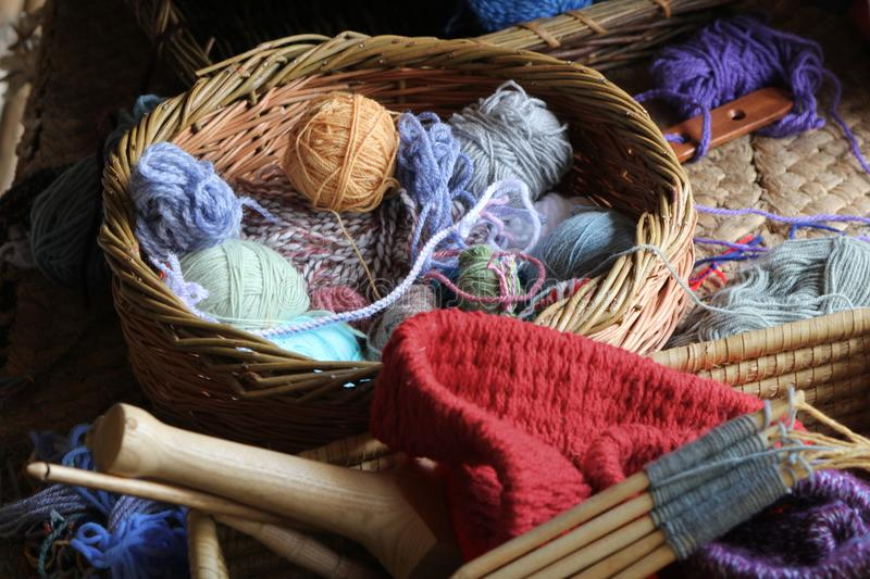 Wool or yarn balls, and knitting needles, in a traditional wicker craft basket royalty free stock image