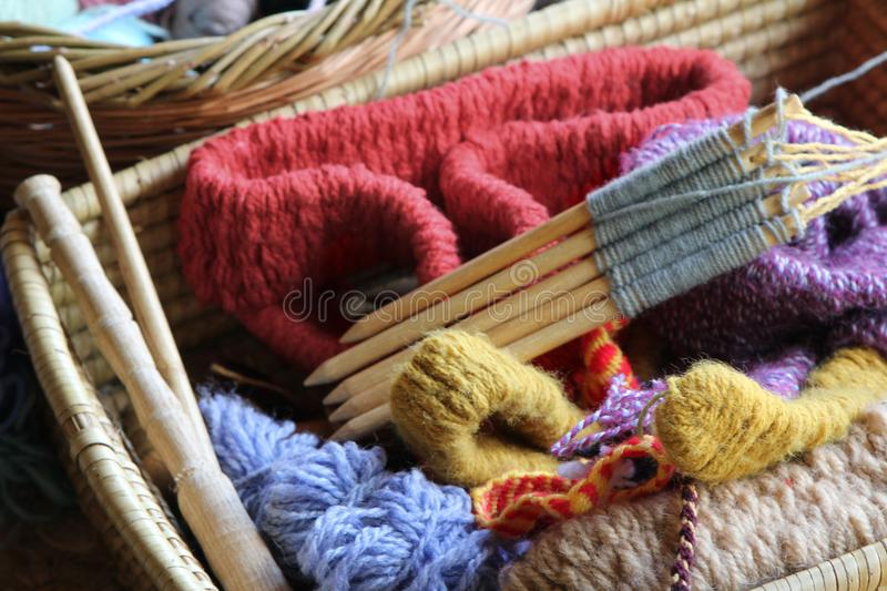 Wool or yarn balls, and knitting needles, in a traditional wicker craft basket royalty free stock photo