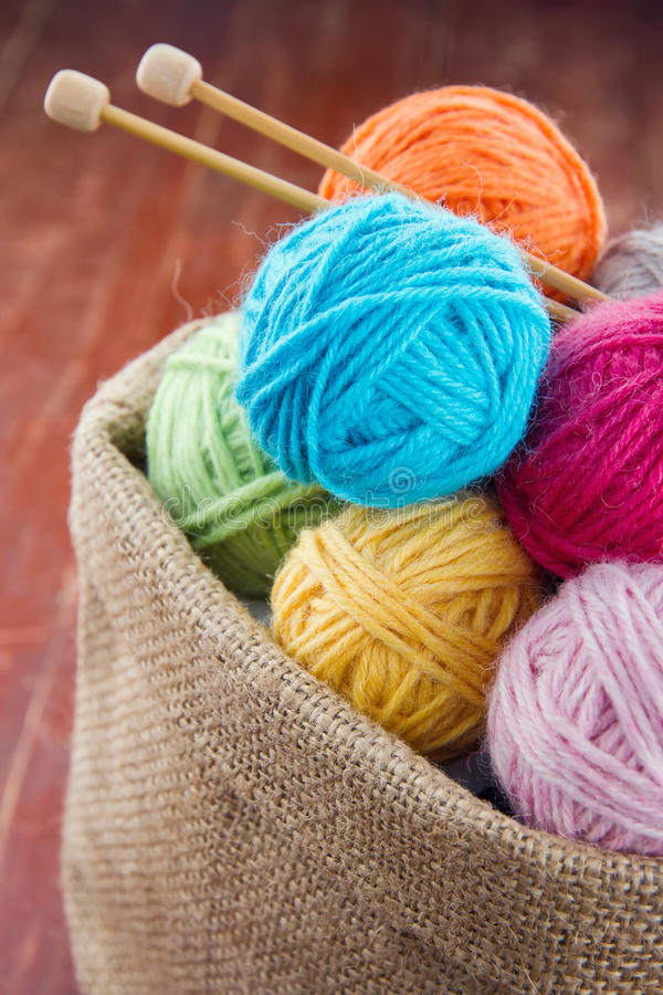 Woolen balls of yarn in a rustic craft bag royalty free stock photo