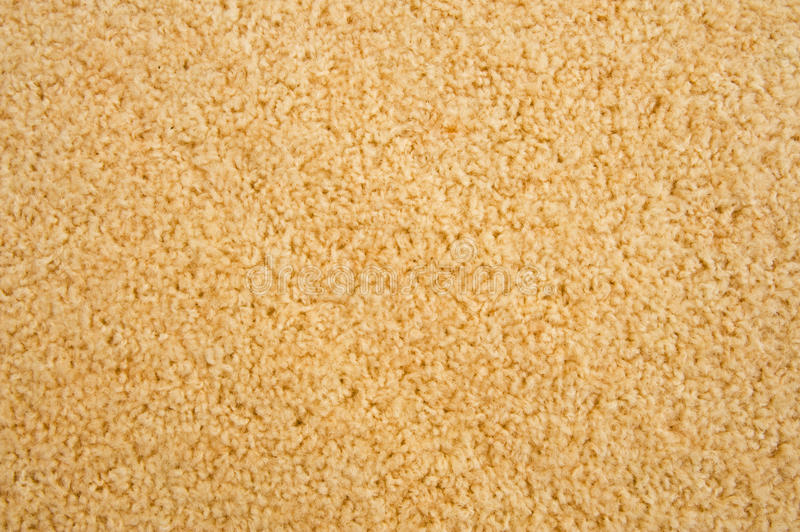 Woolen carpet. A close up image of a beige woolen carpet providing a possible plain background royalty free stock photography